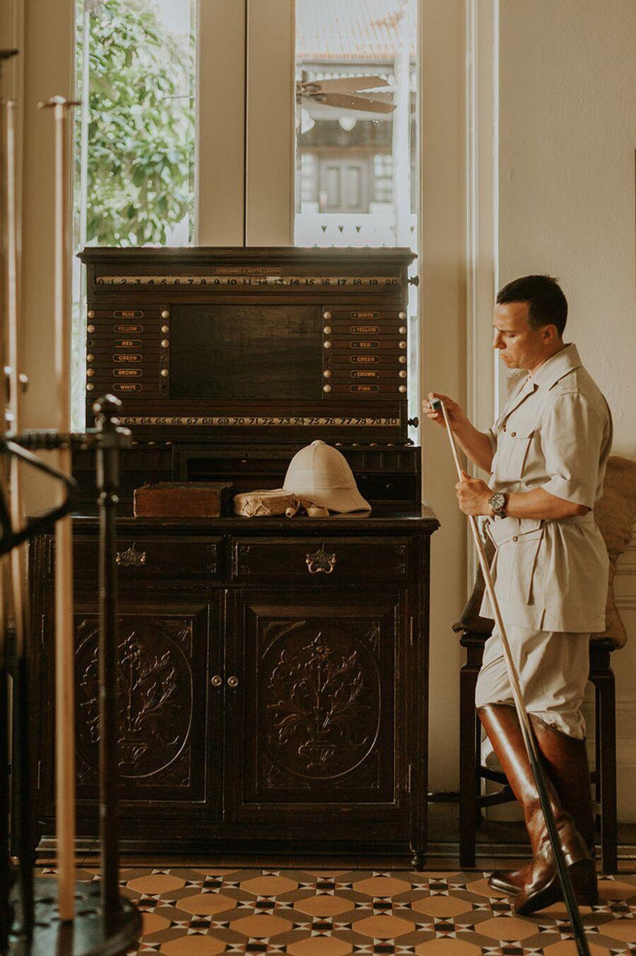 Мужчина готовится играть в бильярд. Raffles Singapore