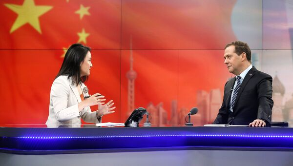 Дмитрий Медведев и ведущая Юань Мин  во время он-лайн конференции в студии штаб-квартиры Шанхайской медиагруппы. 5 ноября 2018
