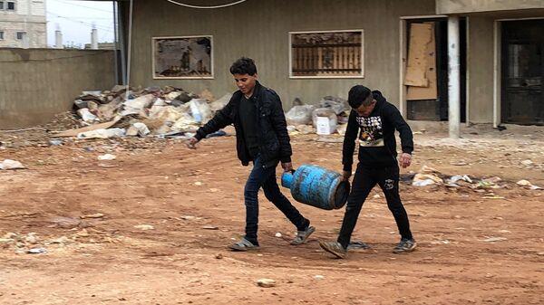 Сирийские беженцы в стихийном палаточном городке в долине Бекаа в Ливане