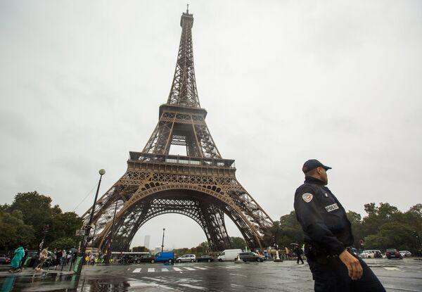 Сотрудник полиции возле Эйфелевой башни в Париже