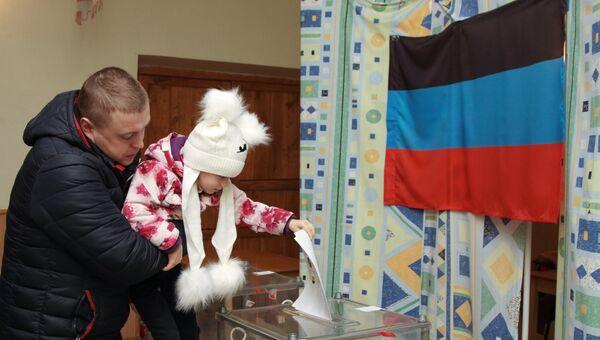 Мужчина с ребенком голосует на выборах главы и депутатов Народного совета ДНР на избирательном участке №57 в Донецке. 11 ноября 2018