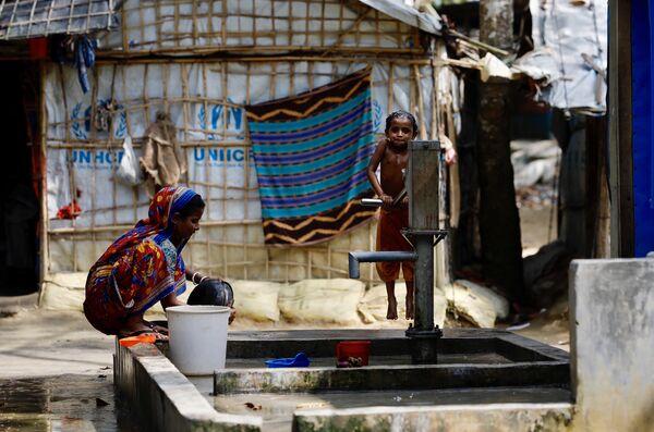 Беженцы рохинджа у водяного насоса в Мьянме