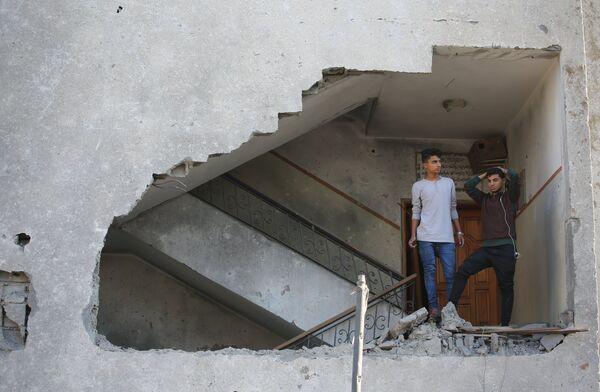 Молодые люди в жилом доме, пострадавшем от ракетного удара Израиля по территории сектора Газа
