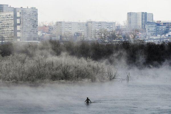 Рыбак в гидрокостюме ловит рыбу на протоке Татышева в Красноярске