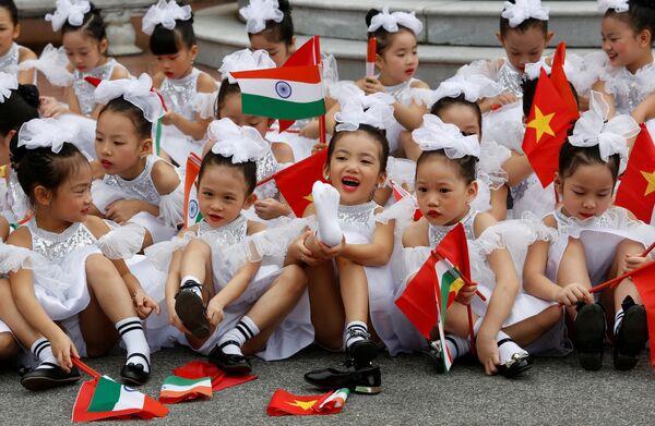 Дети держат индийские и вьетнамские флаги после церемонии приветствия президента Индии Рама Натха Ковинда в Президентском дворце в Ханое