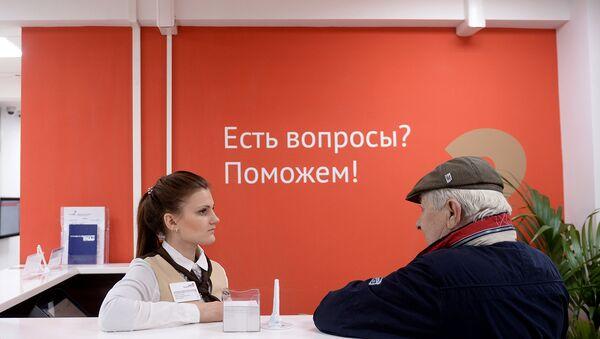 Сотрудница и посетитель центра государственных услуг. Архивное фото