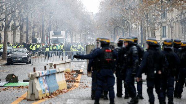 Сотрудники полиции применяют слезоточивый газ во время акции Желтые жилеты в Париже, Франция. 1 декабря 2018