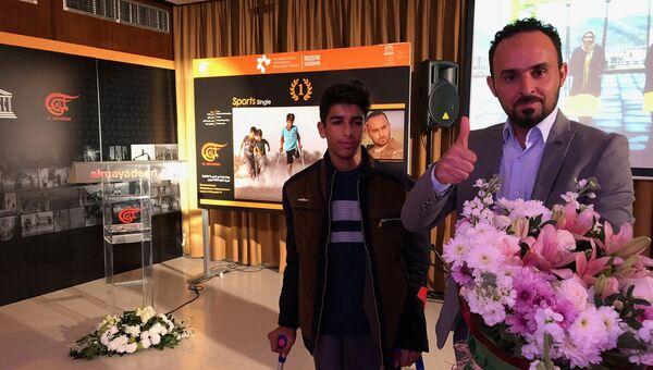 Победитель конкурса в номинации спорт иракский фотограф Таисир Мехди и герой его фотографии мальчик Касим на фоне самой фотографии. 3 декабря 2018