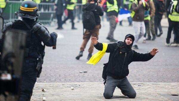 Сотрудник правоохранительных органов и активист во время протестной акции движения желтые жилеты в Париже. Архивное фото