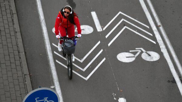 Девушка едет на велосипеде по улице в Москве