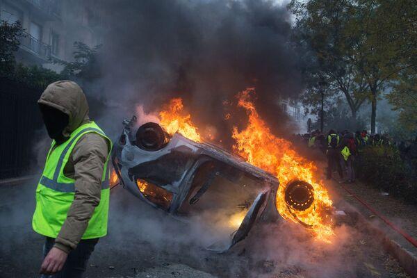 Автомобиль, горящий во время протестной акции движения автомобилистов желтые жилеты, выступавшего с требованием снижения налогов на топливо, в районе Триумфальной арки в Париже