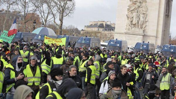 Участники акции протеста движения автомобилистов желтые жилеты в районе Триумфальной арки в Париже.  8 декабря 2018