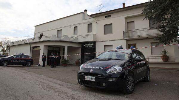 Полицейские перед входом в клуб Lanterna Azzurra в городе Коринальдо, где шесть человек погибли в давке во время концерта. 8 декабря 2018