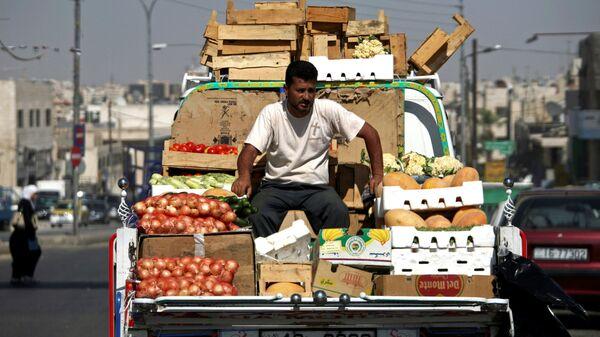 Продавец овощей и фруктов на рынке в Иордании