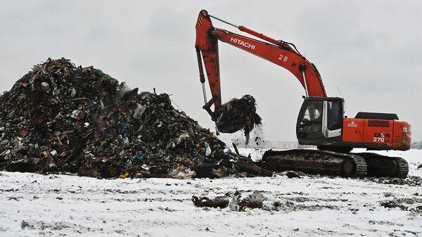 Экскаватор на полигоне твердых бытовых отходов