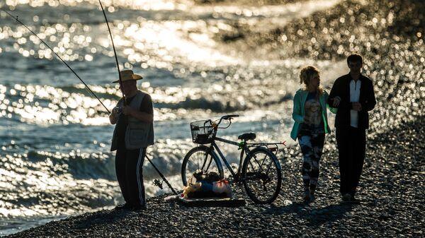 Люди отдыхают на набережной