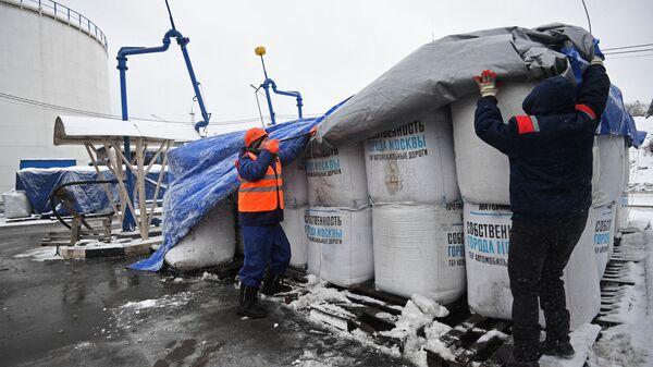 Сотрудники ГБУ Автомобильные дороги распаковывают мешки с сухим противогололедным материалом