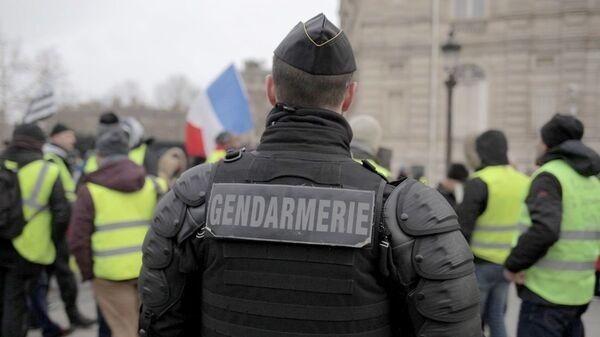 Сотрудник полиции во время акции протеста движения автомобилистов желтые жилеты в районе Триумфальной арки в Париже. 15 декабря 2018