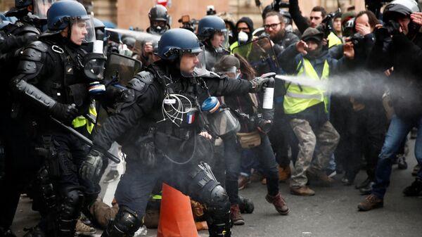Полиция использует перцовый баллончик против протестующих в желтых жилетах возле Оперы Гарнье в Париже, Франция. 15 декабря 2018