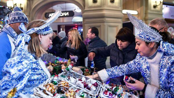 Продавцы елочных игрушек в торговом центре ГУМ в Москве