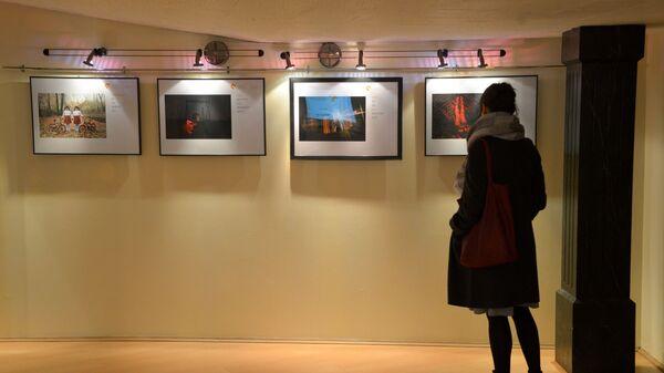Посетительница знакомится с экспозицией на открытии выставки победителей конкурса имени Андрея Стенина в Брюсселе