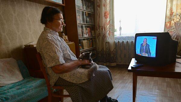 Пенсионерка смотрит прямую трансляцию ежегодной большой пресс-конференции президента РФ Владимира Путина