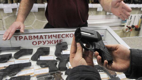 Покупатель осматривает травматический пистолет Оса в оружейном магазине