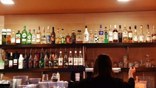 Алкогольные напитки и сиропы на полках бара