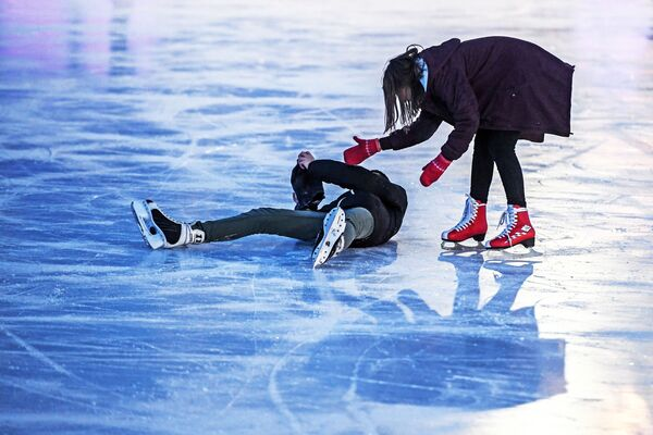 Посетители катаются на катке с искусственным льдом в парке Сокольники в Москве