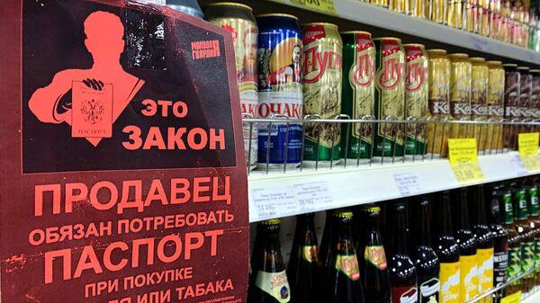 Листовка с надписью Продавец обязан потребовать паспорт при покупке алкоголя или табака на полке с алкогольными напитками в магазине
