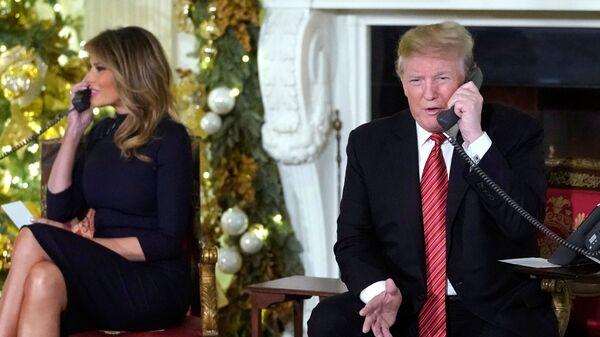 Президент США Дональд Трамп и первая леди Меланья Трамп во время рождественской горячей линии. 24 декабря 2018