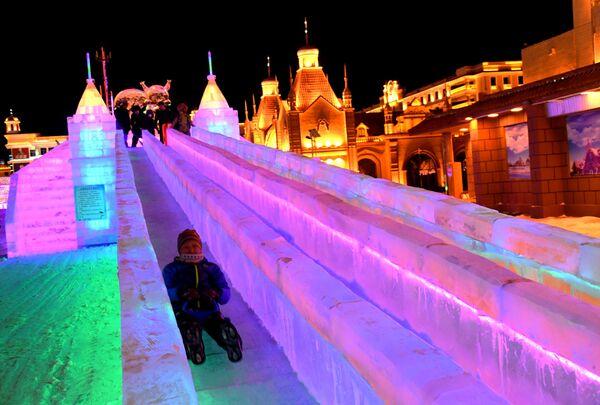 Дети катаются с ледяной горки на международном фестивале снега и льда в городе Маньчжурия