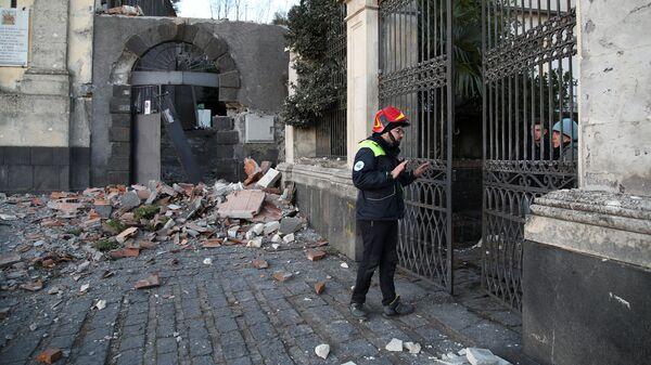 Спасатель общается с жителями Сицилии после землетрясения. 26 декабря 2018