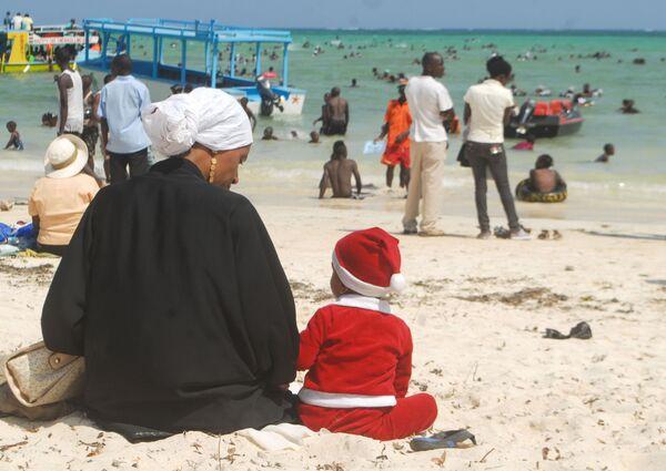 Мальчик в костюме Санты сидит рядом со своей матерью на пляже в Момбаса, Кения