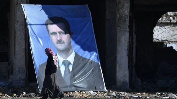 Мужчина у портрета президента Сирийской арабской республики Башара Асада на окраине сирийского Алеппо