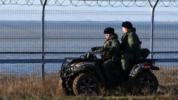 Российские пограничники у заграждения, возведенного в Крыму на границе с Украиной