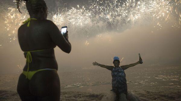Женщины во время встречи Нового года на пляже Копакабана в Рио-де-Жанейро, Бразилия
