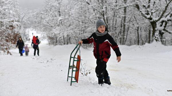 Мальчик с санками на Ангарском перевале в Крыму