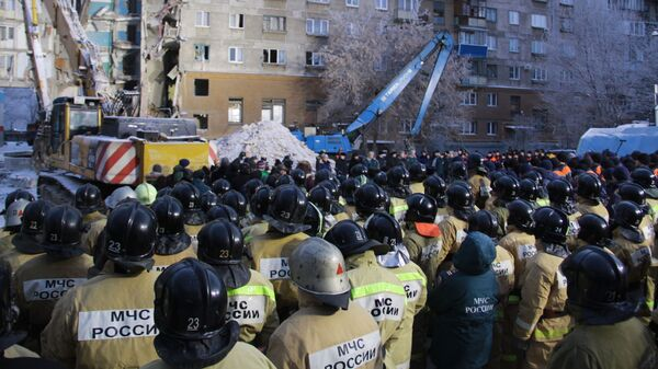 Сотрудники МЧС РФ во время минуты молчания по погибшим после обрушения одного из подъездов жилого дома в Магнитогорске. 4 января 2019