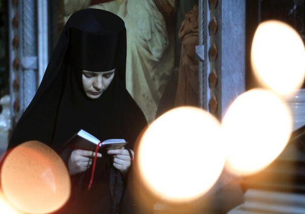 Монахиня перед Рождественским богослужением в храме Христа Спасителя в Москве. 6 января 2018