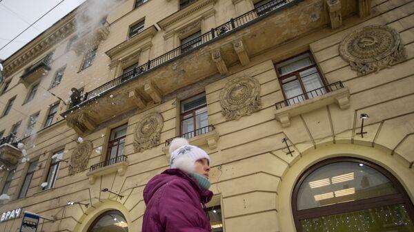 Женщина идет по Суворовскому проспекту в Санкт-Петербурге, где работники коммунальных служб убирают снег с крыш домов