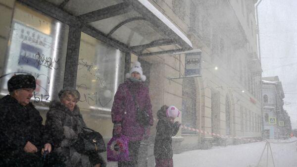 Пассажиры на остановке на Суворовском проспекте, где работники коммунальных служб убирают снег с крыш домов