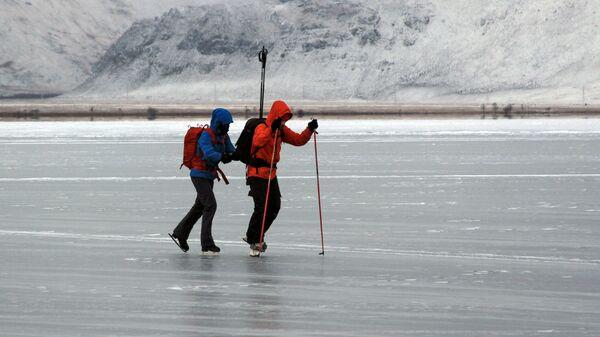Туристы катаются на коньках по льду замерзшего озера Байкал