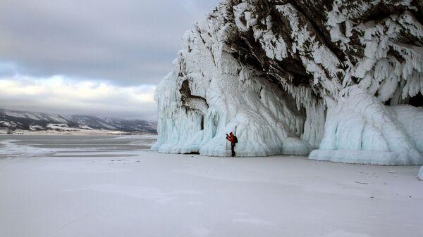 Турист катается на коньках по льду замерзшего озера Байкал