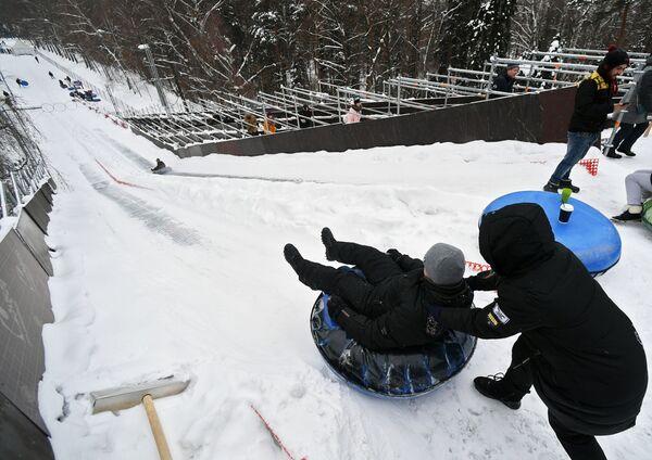Посетители катаются на тюбингах с горки Всепогорка в парке Сокольники