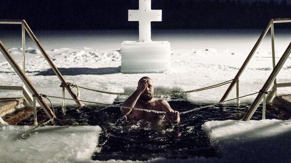 Мужчина во время традиционного праздничного купания в Крещенский сочельник