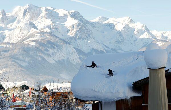 Военнослужащие вооруженных сил Австрии чистят крышу после сильного снегопада в Верфенвенге