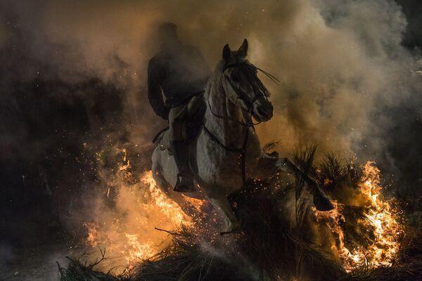 Всадник проезжает через огонь во время ежегодного фестиваля Las Luminarias в испанской деревне Сан-Бартоломе-де-Пинаре