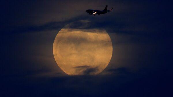 Самолет на фоне лунного затмения в небе над Сан-Диего, США