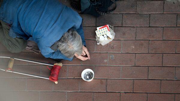 Мужчина просит милостыню в Шанхае
